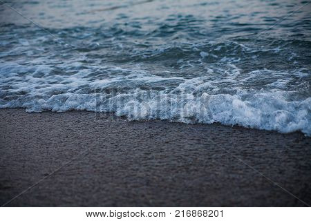 sea wave is swashing on to beach. Evening time
