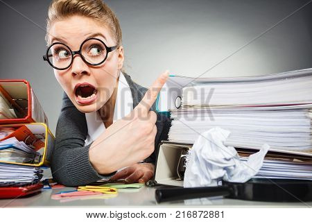 Message and news concept. Emotional stressed scared businesswoman pointing to blank copy space above documents.