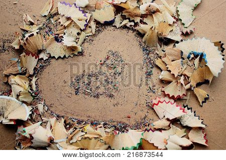 The texture of pencil shavings of red, purple, green and blue colors. Heart shape, lined with shavings. Multicolored pattern on a background of brown cardboard.