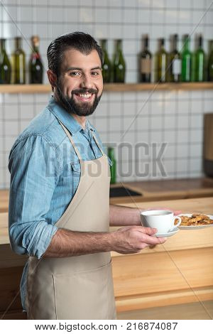 Tasty breakfast. Professional cheerful young waiter looking friendly while standing near the bar counter and holding a cup of hot coffee and a plate of tasty cookies in his hands