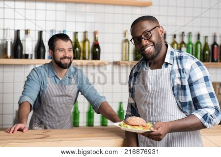 Working together. Positive young cheerful waiter holding a plate with a tasty fresh sandwich while his friendly colleague standing at the bar counter and looking at him