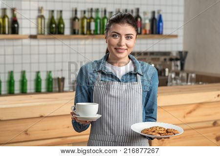 Cute waitress. Pleasant young beautiful waitress being professional while standing in a cafe and holding a cup of coffee and a plate with tasty cookies in her hands poster