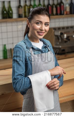 Skilled waitress. Professional skilled young waitress looking friendly while standing at the bar counter with a clean white towel on her right arm and smiling cheerfully