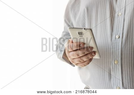 A business man is is holding on to his white cellphone. The background is all white. The businessman is wearing a button down white striped shirt.