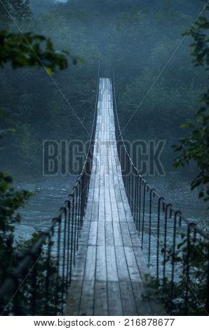 Suspension bridge. Suspension bridge bridge over a mountain stream.