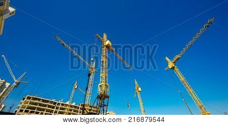Large construction cranes. High and heavy construction machinery. Construction of  houses. Urbanization is the process of urban growth.
