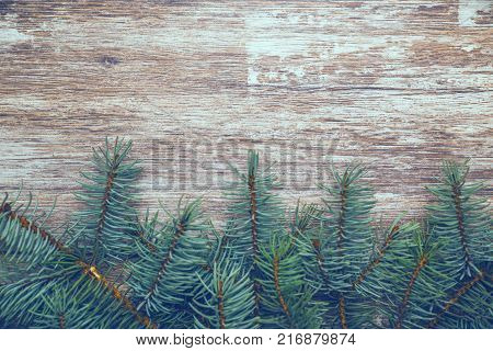 Vintage christmas background. Fir tree branches on old boards. New Year background. Xmax background. Christmas tree. Toned image. Vintage image.