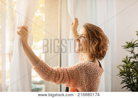 Beautiful woman opening curtains at home