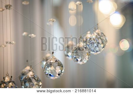 Background with glass hanging balls and luminous the bokeh.  Decorative faceted transparent sphere. Festive luxury interior element.