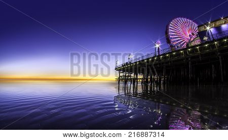 Panorama of Santa Monica Pier alonf the Pacific Ocean in Los Angeles California with blue sky for text space or copyspace. The image depicts nature and tourism in west coast of USA