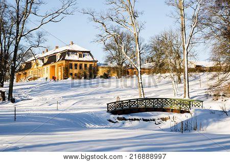 Wooden arch footbridge on a snow covered landscape. Bogstadvannet area in Oslo Norway. Winterscape
