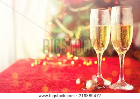 Two glasses of champagne near beautiful christmas tree. Pouring champagne into glass. Merry Christmas and Happy New Year. Moody style. Selective focus.