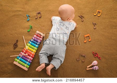 Cute boy with xylophone on color textile