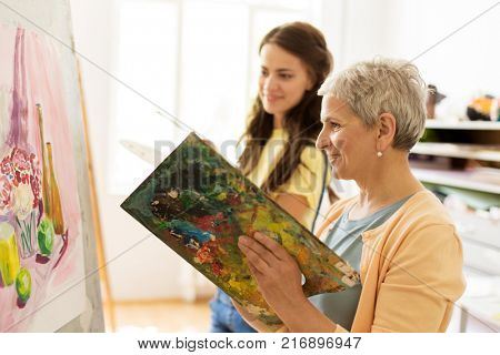 creativity, education and people concept - happy women with brushes and palettes painting still life picture on easel at art school studio