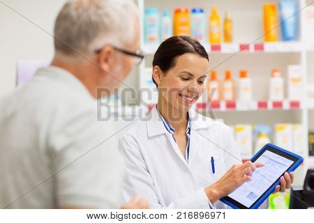 medicine, pharmaceutics, healthcare and technology concept - happy apothecary and senior customer with tablet pc computer at pharmacy