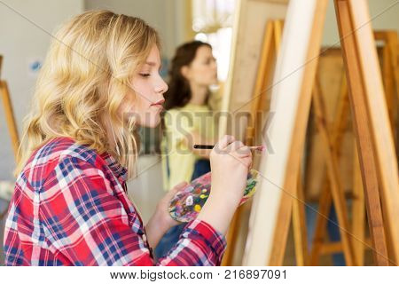art school, creativity and people concept - teenage girl with easel, palette and brush painting at studio