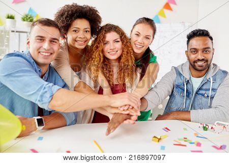 teamwork, success and celebration concept - happy business team holding hands together at office corporate party