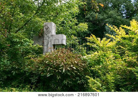 Stone grave cross in the cemetery among the trees