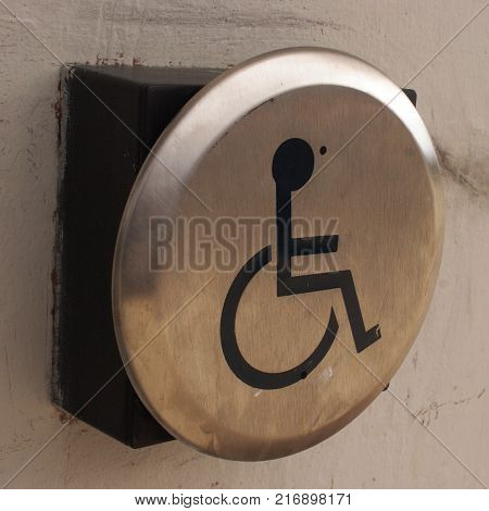 Square format of a closeup view on a disability door accessibility button.
