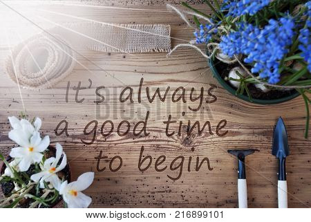 English Quote It Is Always A Good Time To Begin. Sunny Spring Flowers Like Grape Hyacinth And Crocus. Gardening Tools Like Rake And Shovel. Hemp Fabric Ribbon. Aged Wooden Background
