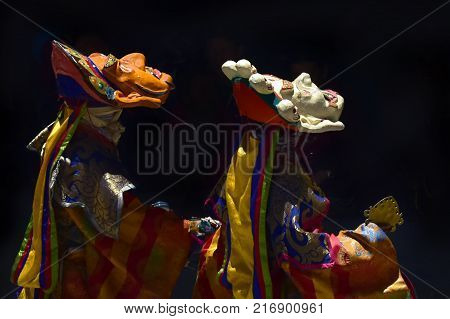 The dance of Buddhist lamas in masks: two monks perform an ancient Tibetan ritual, masks are dressed on the head and face up.