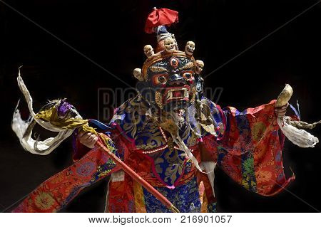 Buddhist monk performs a dance mask in an ancient wooden mask of a blue color with white skulls on top of the face and a red flag, bright clothes, the Himalayas.