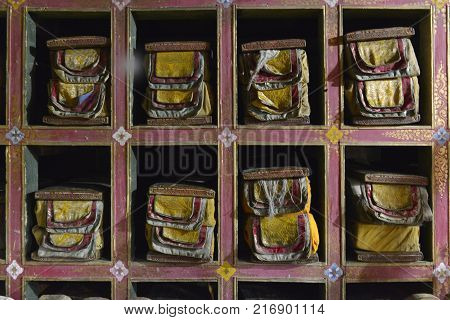 Library of Tibetan books: ancient Tibetan manuscripts wrapped in bright sacral cloths, lie in a special closet in square compartments, Tibet.