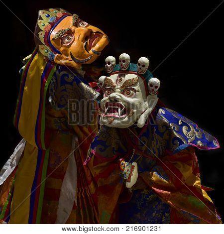 Tibetan sacred mystical clothing: ancient wooden ritual masks White Mahakala and Yellow Shamballa, and bright colored dresses.