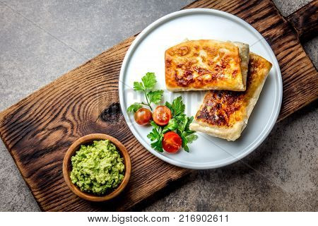 Mexican chimichanga on white plate served with guacamole sauce. Fried tortilla stuffed with chicken and vegetables. Traditional Mexican food, Top view.