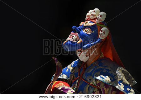 Performers with a Tibetan lama dressed in the ancient mask of Mahakala Blue and bright clothes on a black background.