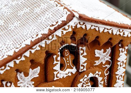 Festive brown gingerbread christmas decoration, with white fancy icing and a ginger bread man