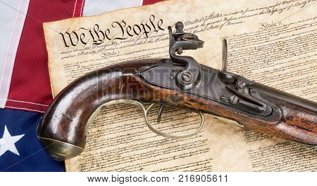 We the People with antique flintlock pistol and American flag.