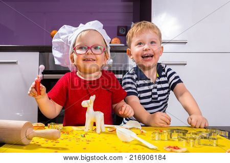 Cute little boy and girl twins preparing Christmas cookies in the kitchen
