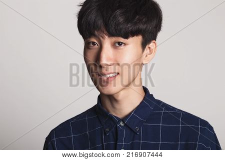 A studio portrait of an Asian young man smiling with a bright smile