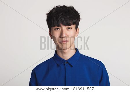 A studio portrait of an Asian man who looks displeased and disappointed