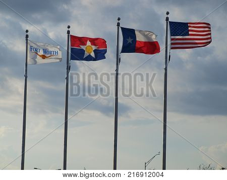 The city flags of Ft. Worth and Dallas and the Texas state flag and the US flag wave at the Official FAA beacon at DFW International's Founder Plaza .