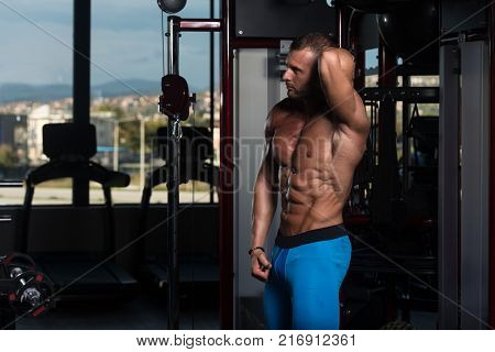 Portrait Of Muscular Man Standing Near The Wall