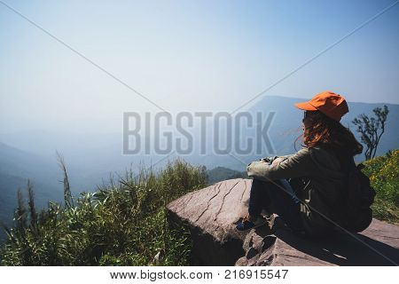 Asian women travel relax in the holiday. Sit and watch landscape on the Moutain. Mountain Park happily. In Thailand