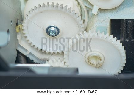 Two white gears connected in the device.