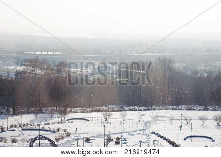 Winter cityscape. Trees, wood, track, snow, industrial pipes.