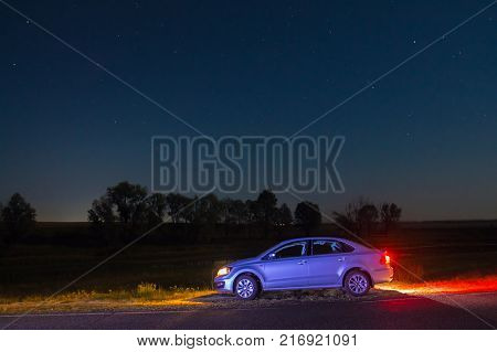 Dobrush, Belarus - August 12, 2017: Car Volkswagen Polo Vento sedan on the roadside with lights on under the starry sky