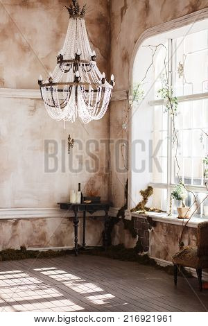 Old fashioned vintage room corner with black table and candles. Dirty walls covered with fern, big crystal ceiling light.