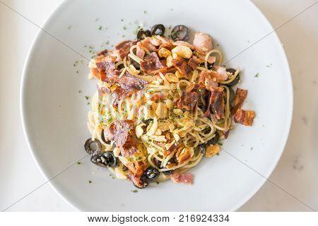 Spaghetti aglio with crispy Bacon on white dish