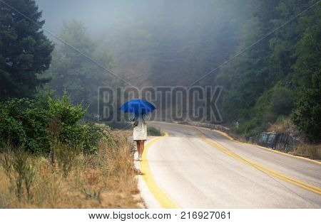 Young female in a raincoat and umbrella on the road in the fog. Travel of women in the raincoat hitchhiking in the rain