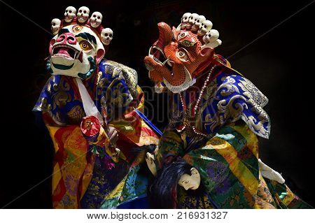 Dance Cham, Dance Buddhist monks high tantric initiations in bright clothes and Masks White Mahakala and orange Makara, Tibet.