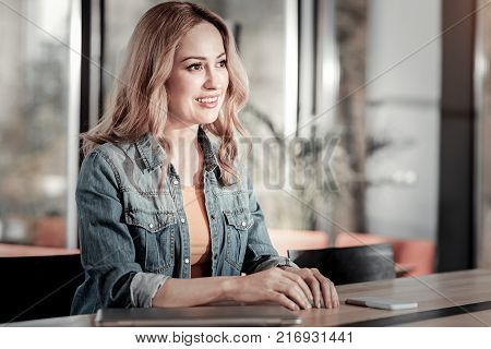 Pleasant woman. Kind friendly beautiful woman looking cheerful while sitting in a nice cafe and waiting for a waiter with her smart phone being on the table by her side