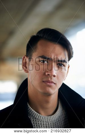 A young man with dark hair and eyes frowns.Reverie. Frowns. Model posing, emotions