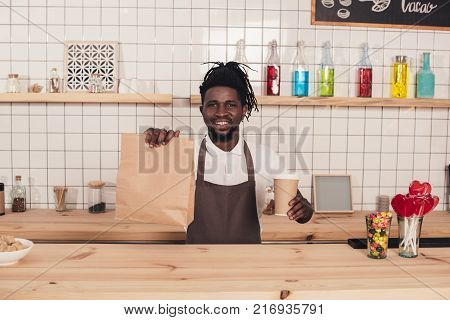 african american barista in apron holding coffee cup while standing at bar counter