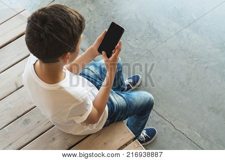 View from above. Boy in white T-shirt and sunglasses sitting indoor and uses smartphone. Teenager plays computer games on digital gadget, surfing internet. Social networks, computer games, e-learning.