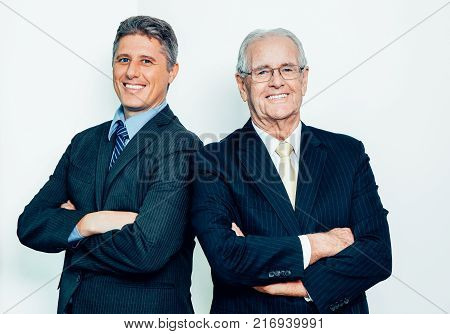 Portrait of two successful senior and mid adult male partners standing with folded arms, looking at camera and smiling